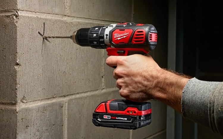 man drills wall with cordless drill