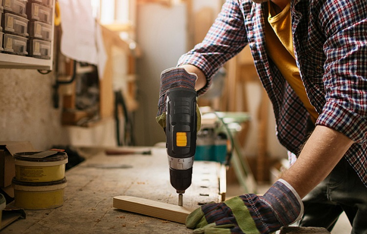 man drills wood with cordless drill