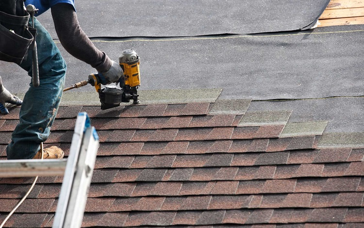 man installing new shingles on roof with nail gun