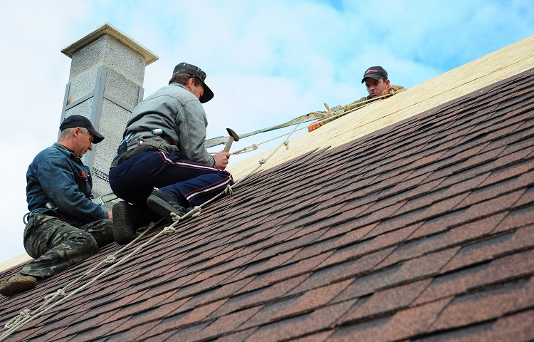 three workers replacing roof